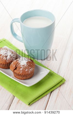 Cup of milk and cakes on white wooden table