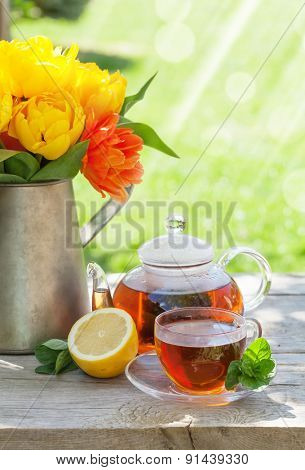Breakfast tea on garden table and colorful tulips bouquet