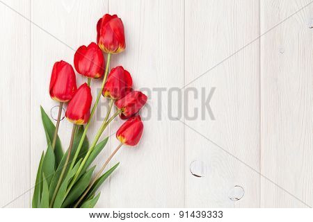 Red tulips bouquet over white wooden table background with copy space