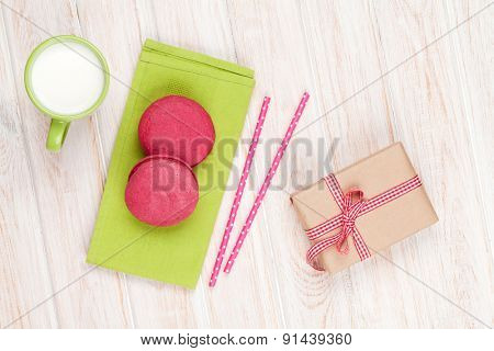 Colorful macarons, cup of milk and gift box on white wooden table