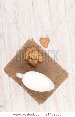 Heart shaped gingerbread cookies and milk pitcher. On white wooden table