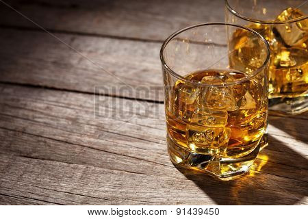 Glasses of whiskey with ice on wooden table with copy space
