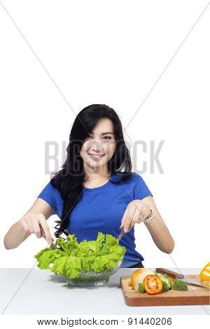 Cheerful Woman Mixing Salad On A Bowl