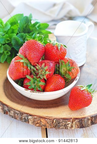 strawberry with cream and mint on a wooden backgraund
