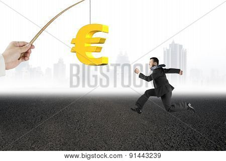 Man Running Golden Euro Symbol Fishing Lure Asphalt Road Cityscape
