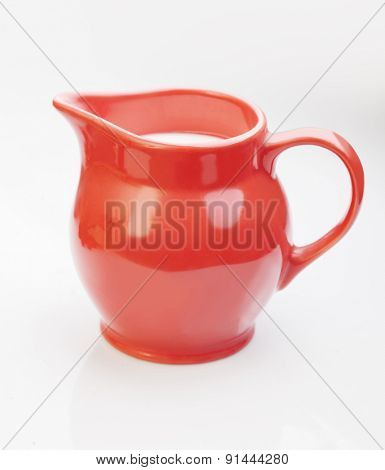 red jug with milk isolate on white