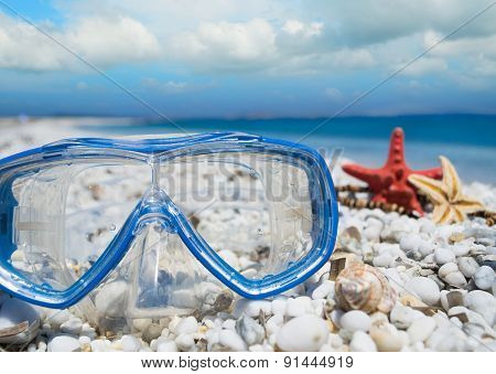 Diving Mask And Shells Under Clouds