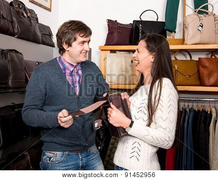 Shop Assistant Showing Leather Bag To Beautiful Woman
