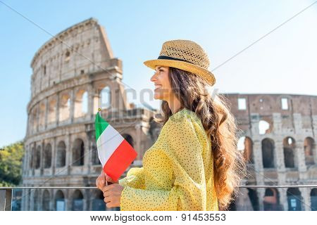 Woman Holding Flag Looking Into Distance At Colosseum In Rome