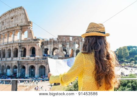 Seen From Behind, A Woman Tourist Holding A Map At Colosseum