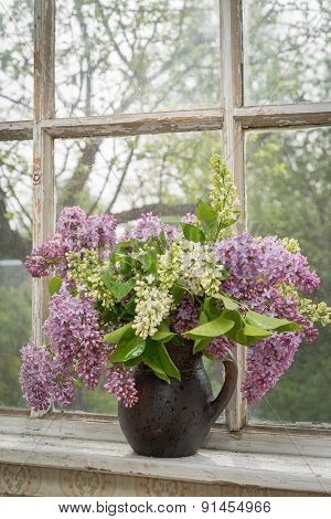 Still Life With Blooming Branche Of Lilac On A Window Sill