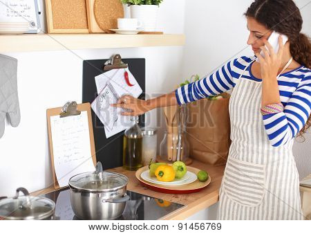 Portrait a smiling woman with phone in kitchen at home