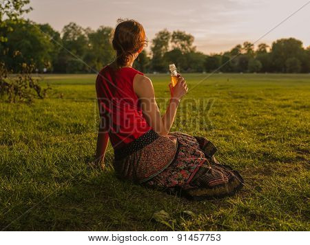 Woman Drinking And Admiring Sunset In Park