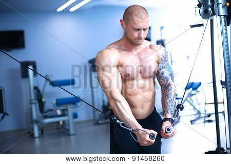 Young man training at gym with exercises
