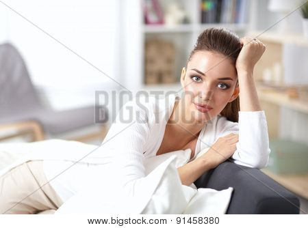 Portrait of beautiful woman sitting on couch at her room .