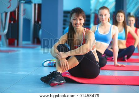 Sporty people sitting on exercise mats at a bright fitness studio
