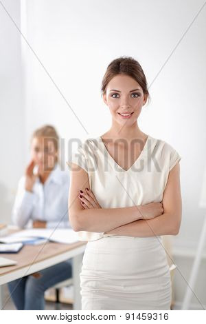 Attractive businesswoman with her arms crossed standing .