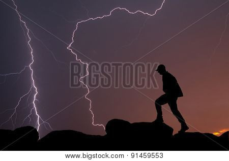 Silhouette of a man climbing on top of a mountain against a colorful sunrise