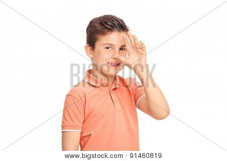Silly little boy making a childish hand gesture and looking at the camera isolated on white background
