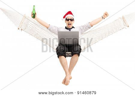 Joyful guy with Santa hat working on a laptop seated in a hammock and drinking beer isolated on white background