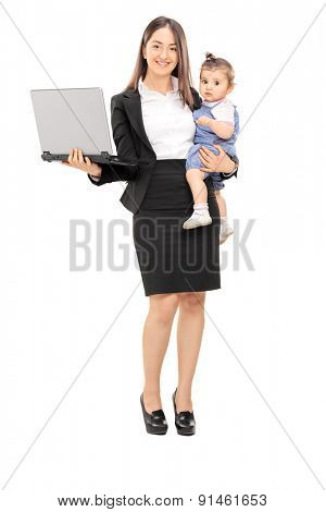Full length portrait of a young businesswoman carrying her daughter in one hand and holding a laptop in the other isolated on white background