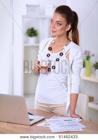 Attractive businesswoman standing  near desk in office