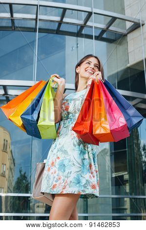 Attractive Woman Posing With Shopping Bags In Front Of The Shopping Center