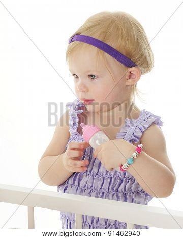 An adorable 2-year-old standing crib-side ready to feed her dolls with a baby bottle.  On a white background.