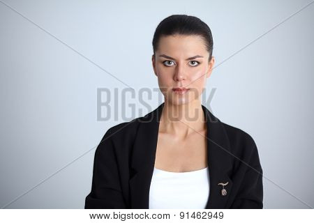 A young woman standing, isolated on graybackground