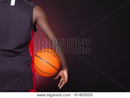 Back view of a basketball player holding a basketball against dark background