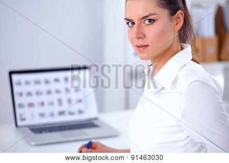 Attractive businesswoman sitting with laptop  in the office