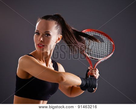 Female tennis player with racket ready to hit a tennis .