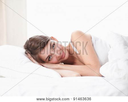 Beautiful girl lying in bedroom at early morning.