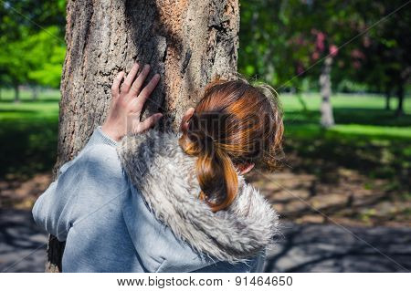Woman Hiding Behind Tree In Park