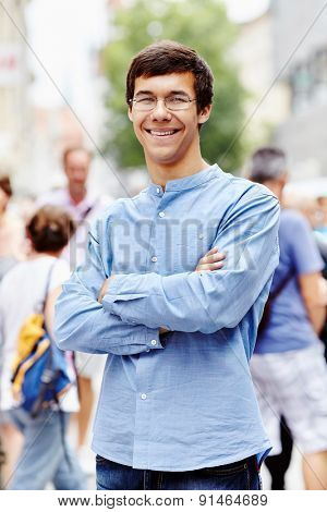 Portrait of smiling guy in glasses with crossed arms at crowded street in a sunny day