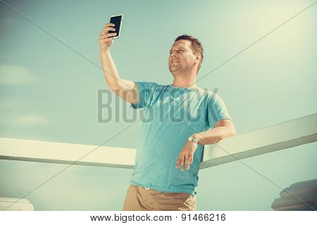 Man Tourist On Pier Taking Selfie With Smartphone.