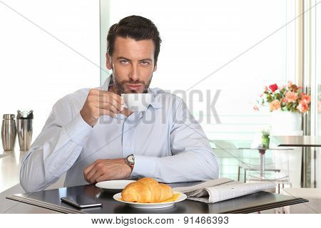 Man Drinking Coffee In Cafe With Croissant And Newspaper On Table