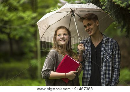 Young couple in the Park under an umbrella, a girl holds a red book in his hands.