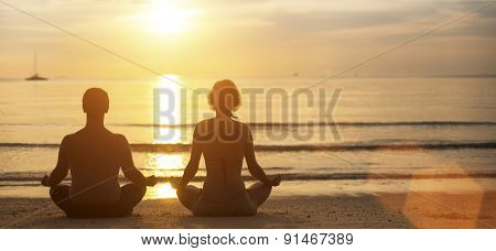Man and woman yoga silhouettes meditating on Sea coast during the sunset.