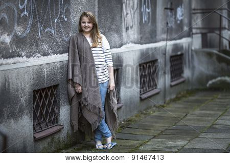 Teenage girl standing in a poncho in the evening on the street.