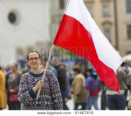 Young woman on the street with the flag of Republic of Poland.
