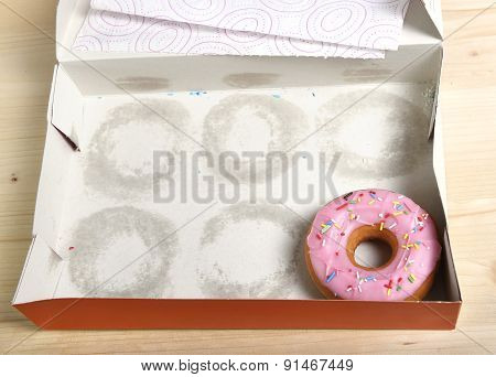 Empty Cakes Box With Only One Tempting And Delicious Donut With Toppings Left