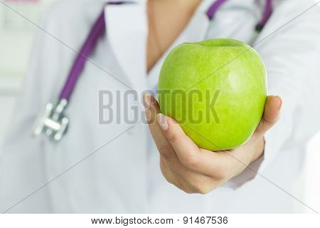 Female Doctor's Hand Holding Fresh Green Apple