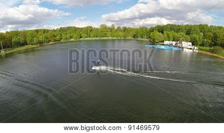 RUSSIA, MOSCOW - MAY 11, 2014: Man rides by Putyaevskii pond and jumps at spring sunny day in city park. Aerial view.