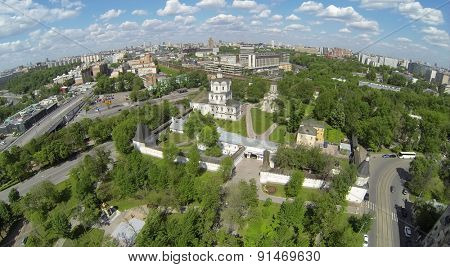 RUSSIA, MOSCOW - MAY 14, 2014: Spaso-Andronikov monastery against city with traffic on river embankment and railroad at sunny day. Aerial view.