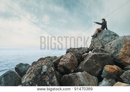 Woman Sitting On Stone Coast