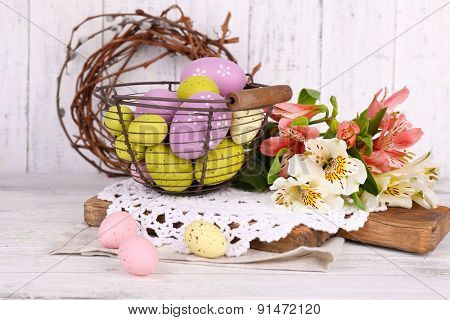 Easter composition with Easter eggs in basket and flowers, on wooden background
