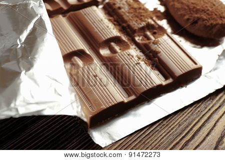 Bar of chocolate with cocoa on foil, closeup