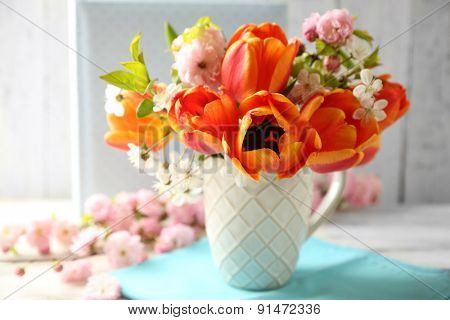 Spring bouquet in colorful mug on color wooden background