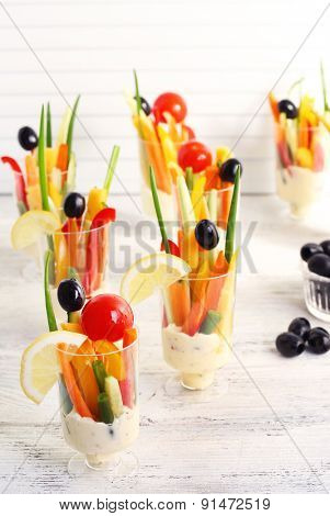 Snack of vegetables in glassware on wooden table on blinds background